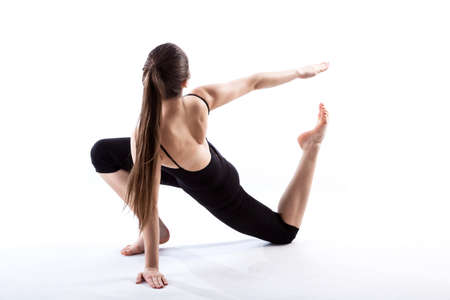 stretched: A fit woman in black stretching her body