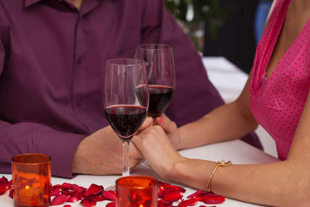 proposing a toast: A man and a woman holfing hands having a glass of red wine