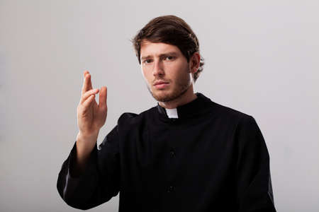 catholic mass: Young christian priest is giving a blessing Stock Photo