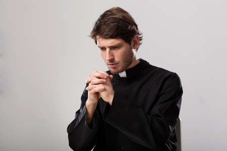 Young christian priest is saying a prayer Stock Photo