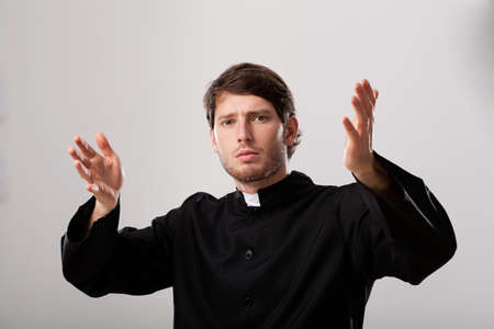 the sermon: Young christian priest is preaching a sermon