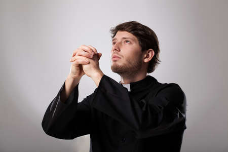 earnestly: Young christian priest is earnestly praying to god