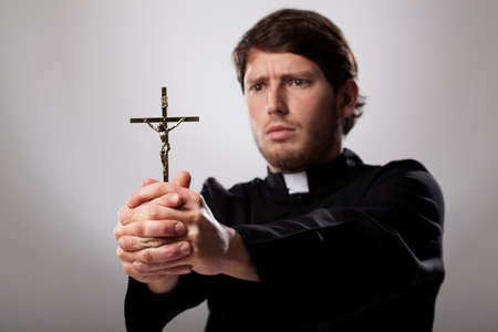 Young christian priest is holding a cross Stock Photo