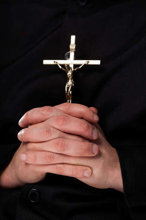 Priest is holding a cross which is a christian symbol photo