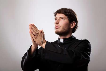sacerdote: Joven sacerdote cristiano reza el rosario