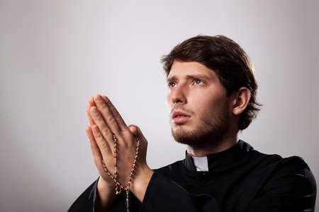 Young priest is earnestly praying the rosary