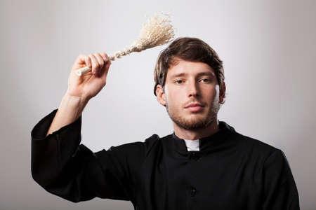 젊은 기독교 사제는 스프링 클 러를 잡고있다.