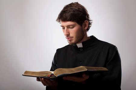 若いキリスト教の司祭は神聖な聖書を読んでください。