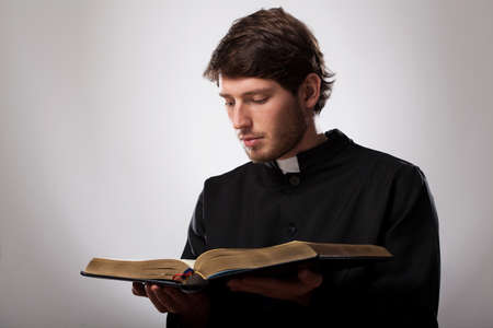 Young christian priest is reading the Holy Bible