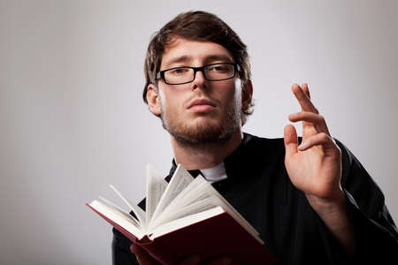 Young christian priest in glasses with Holly Bible