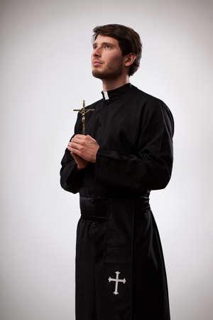 sacerdote: Joven sacerdote cristiano está de pie y sosteniendo una cruz