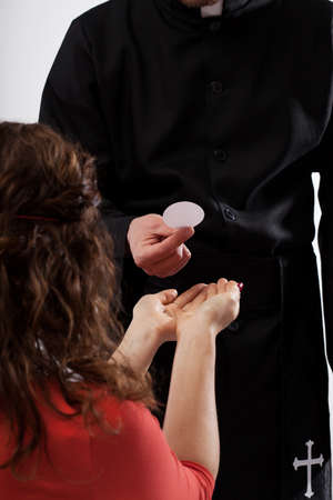 catholic mass: Catholic priest and female believer during eucharist Stock Photo