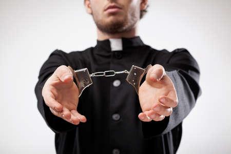 sotana: Joven sacerdote cristiano en sotana arrestado y esposado Foto de archivo