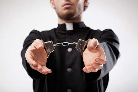 Young christian priest in cassock arrested and handcuffed Stock Photo