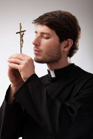Youn christian priest is praying to cross