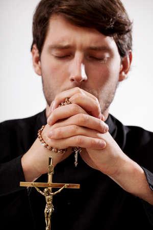 różaniec: Młody chrześcijanin kapłan modli się na różańcu