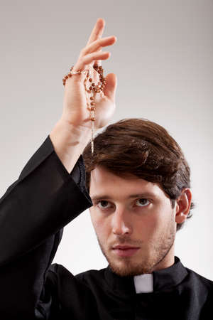 Young christian priest is holding a rosary