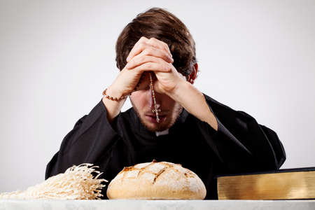 Young christian priest is praying and blessing