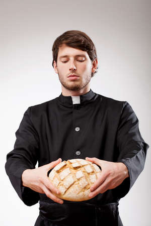 Young christian priest is blessing the bread