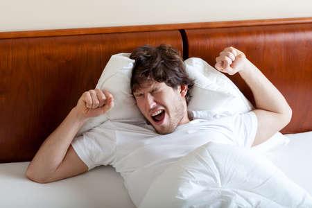 Young yawning man after awakening in bed
