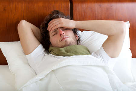 Young man having cold lying in bed, horizontal Stock Photo