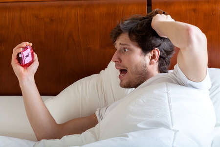 oversleep: Late man in bed after awakening, horizontal Stock Photo