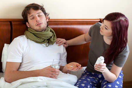 Young wife looking after her ill husband Stock Photo - 26578052
