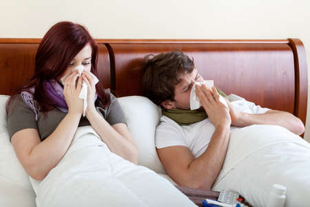 running nose: Marriage with running nose lying in bed Stock Photo