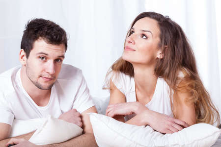 contraception: Pretty wife and handsome husband in bed