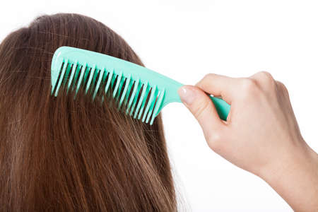 Girl with brown strong and straight hair combing herself Stock Photo