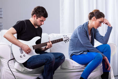 Rockman during playing guitar and bored woman