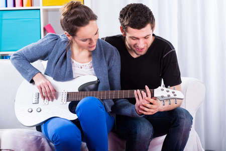 man playing guitar: Couple learning to play the guitar, horizontal
