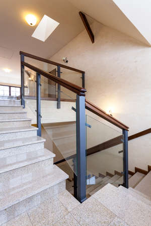 Staircase with stone steps and glass banister photo