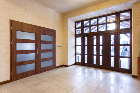furnish: Entrance to a spacious hall with wooden door