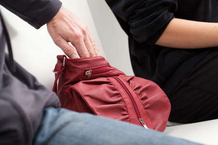 swindler: A thief slipping his hand into a womans red leather bag