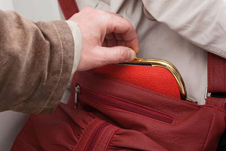 A close up of a man stealing a red purse Stock Photo