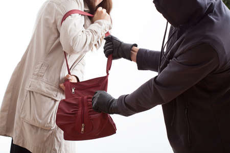 A thief taking a womans bag off her shoulder photo