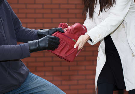 red purse: A thief yanking a red bag from a woman in front of a brick wall Stock Photo