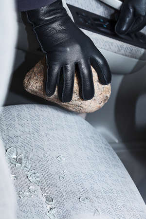 A hand in a glove holding a stone after breaking into a car photo
