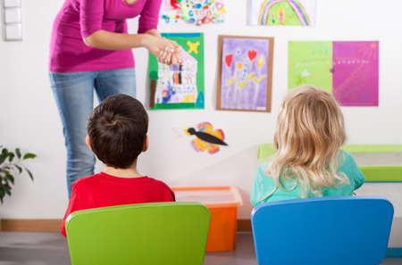 Good pupils listening to their kindergarden teacher