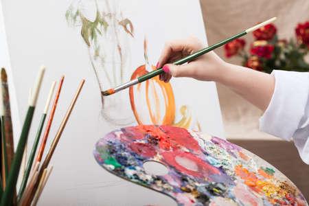 Een close-up van een kunstenaar met een penseel schilderen van een foto Stockfoto