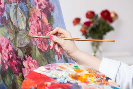 A closeup of an artist painting flowers using a brush and a palette photo