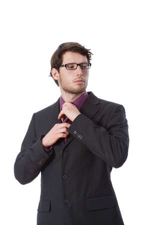 Serious businessman during checking his tie, vertical