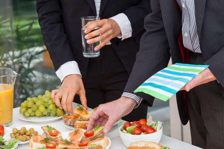 Business people eating lunch at office buffet Stock Photo