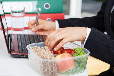 Woman working and eating at office desk photo