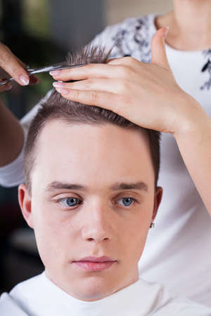 proffesional: Proffesional hairdresser cutting young mans hair in beauty studio