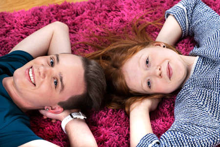 Two happy teenagers friends lying together on carpet Stock Photo - 26806836