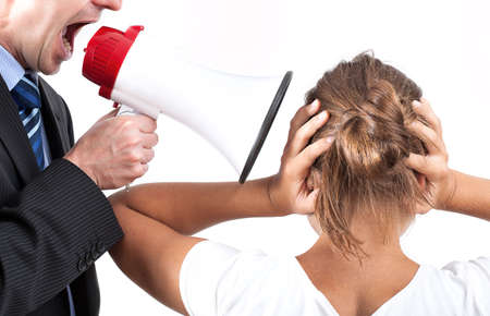 Businessman is yelling through a megaphone, his victim is also his employee photo