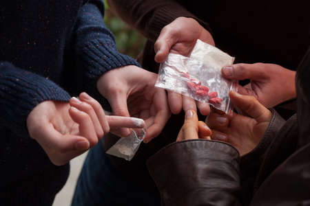 Handen houden gram en tabbladen van drugs Stockfoto