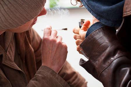 joven fumando: Dos jóvenes vestidos con chaquetas de los fumadores fumar en las articulaciones